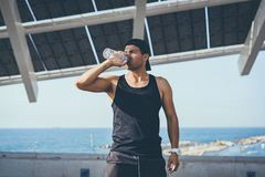 Muscular Male athlete sprinter drinking pure water after hard workout exercise. Healthy lifestyle. stock photo