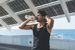 Muscular Male athlete sprinter drinking pure water after hard workout exercise. Healthy lifestyle. Muscular Male athlete sprinter drinking pure water after hard royalty free stock images
