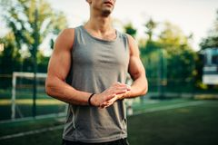 Muscular male athlete on training, fitness workout. Strong sportsman in park Stock Photos