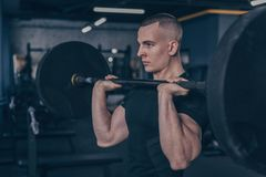 Muscular male athlete working out with barbell at gym studio royalty free stock images