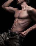Man. Vertical photo of a muscular young man body, on black background. He wears unbuttoned jeans. His arm and chest is the main subject of the photo. He has no