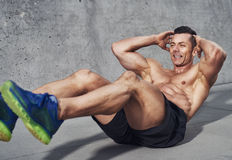 Muscular male fitness athlete doing sit ups while smiling Royalty Free Stock Image