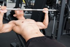 Muscular male having pain on shoulder in gym.  young man injure Stock Photo