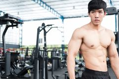 Muscular male having pain on shoulder in gym.  young man injure Stock Photos