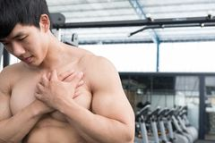 Muscular male having pain on shoulder in gym.  young man injure Royalty Free Stock Photography