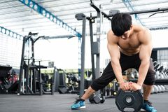 Muscular male having pain on shoulder in gym.  young man injure Royalty Free Stock Photos