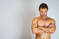 Muscular male model with arms folded. Royalty Free Stock Photography