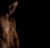 Muscular male model on black background. Royalty Free Stock Photography