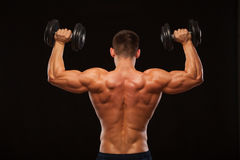 Muscular male model bodybuilder doing exercises with dumbbells, turned back. Isolated on black background with copyspace Stock Photos