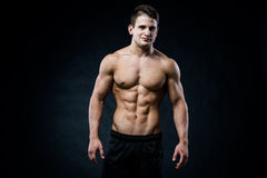 Muscular male model bodybuilder looking straight to the camera. on black. stock image