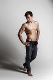 Muscular male model bodybuilder with unbuttoned jeans. Studio sh Royalty Free Stock Photos