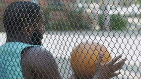 Muscular male sitting near playground net bouncing, waiting for team players. Stock footage stock video