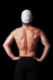 Muscular male swimmer posing from behind with full equipment. Male swimmer isolated on black Royalty Free Stock Photography