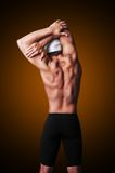 Muscular male swimmer posing and doing stretching. Male swimmer is doing stretching Royalty Free Stock Images