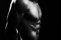 Muscular male torso. Closeup view of one handsome sexual strong young male bare chest of muscular body standing posing on studio background black and white Royalty Free Stock Images