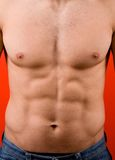 Muscular male torso isolated on red background Stock Photo