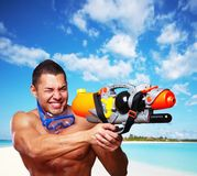 Muscular male with water gun. Portrait of muscular male on a beach with hight pressure water toy gun Royalty Free Stock Photos