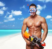 Muscular male with water gun. Portrait of muscular male on a beach with hight pressure water toy gun Stock Images
