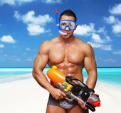 Muscular male with water gun. Portrait of muscular male on a beach with hight pressure water toy gun Royalty Free Stock Images