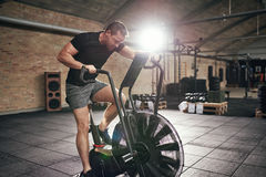 Muscular male working out on cycling machine. Young muscular man in sportswear sitting on cycling machine and riding fast in modern gym Royalty Free Stock Photography