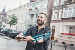 Man working out in the city. Healthy regimen. Muscular male working out outdoors, looking happy and joyful, enjoying his activity, exercising using gym equipment Royalty Free Stock Images