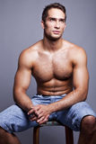 Muscular man. Sitting on a chair Stock Images