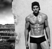 Muscular man against wall with Rome in background Stock Photography
