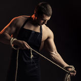 Muscular man in apron with rope Stock Photos