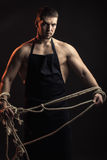 Muscular man in apron with rope Royalty Free Stock Photography