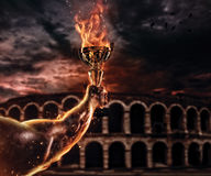 Muscular man arm holding burning trophy cup, antique colosseum o stock photos