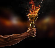 Muscular man arm holding burning trophy cup on black background stock image