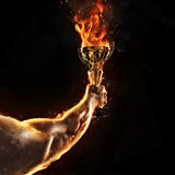 Muscular man arm holding burning trophy cup on black background stock photo