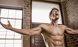 Muscular man with arms stretched. At the gym Royalty Free Stock Photos
