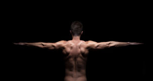 Muscular man with arms stretched out on black background