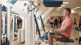 The muscular man athlete is working out at the leg curl machine in the fitness center. 4k footage. The muscular man athlete is working out at the leg curl stock footage