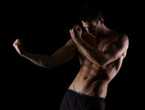 Muscular man in attack pose on black Stock Photo