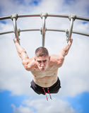 Muscular man bar fitness workout. Outdoor training fitness workout, muscular male / man working out on park bar upside down Stock Photos
