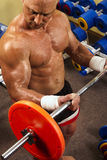 Muscular man with a bar weights in hands training. Fitness - powerful muscular man with a bar weights in hands training Stock Photography