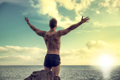 Muscular man on the beach in front of rising sun. Muscular young man on the beach seen from the back, with arms open enjoying the sensation of freedom in front stock image
