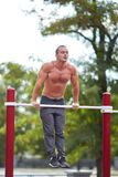 Handsome muscular man doing pull-ups on horizontal bars on a park background. Street sports concept. Stock Photos