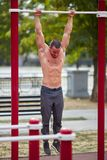Handsome muscular man doing pull-ups on horizontal bars on a park background. Street sports concept. Royalty Free Stock Images