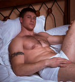 Muscular man in a bed Stock Photos