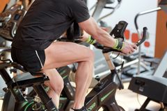 Free Muscular Man Biking In The Gym, Exercising Legs Doing Cardio Workout Cycling Bikes, Spinning Class. Stock Photography - 146757182