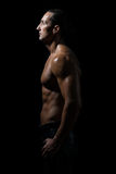 Muscular man in a black background Royalty Free Stock Photos