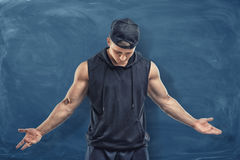 Muscular man in black clothes and cap with his head lowered on blue chalkboard background. Fitness and working out. Healthy living. Sport achievements royalty free stock photo