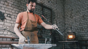 Muscular man blacksmith with hammer in forge creating steel knife Stock Images