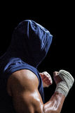 Muscular man in blue hood with fighting stance. Against black background stock photography