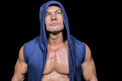 Muscular man in blue hood looking up Stock Photography