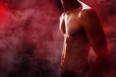 Muscular man body. With smoke background Stock Photo
