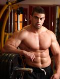 Muscular man. (bodybuilder) in gym (fitness) with weights portrait shot Stock Image